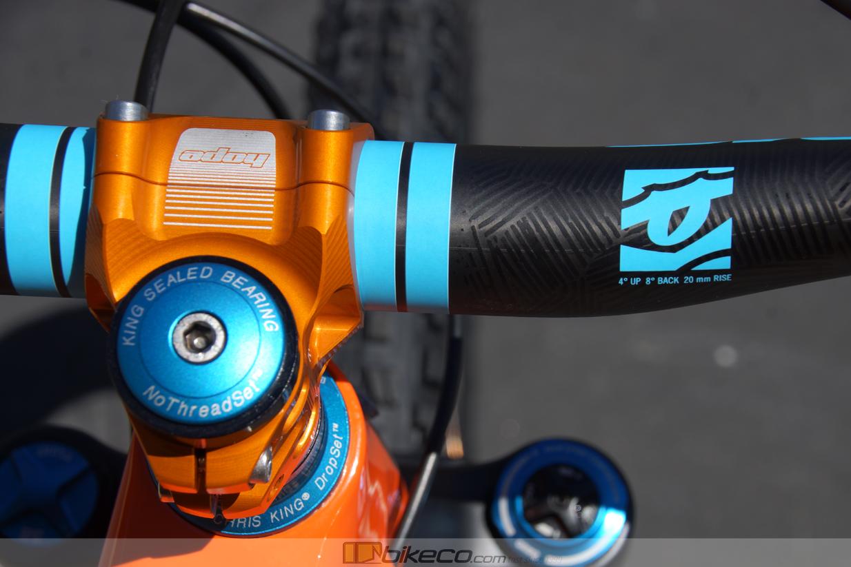 Detail of orange hope stem, matte turquoise chris king headset and raceface handlebar