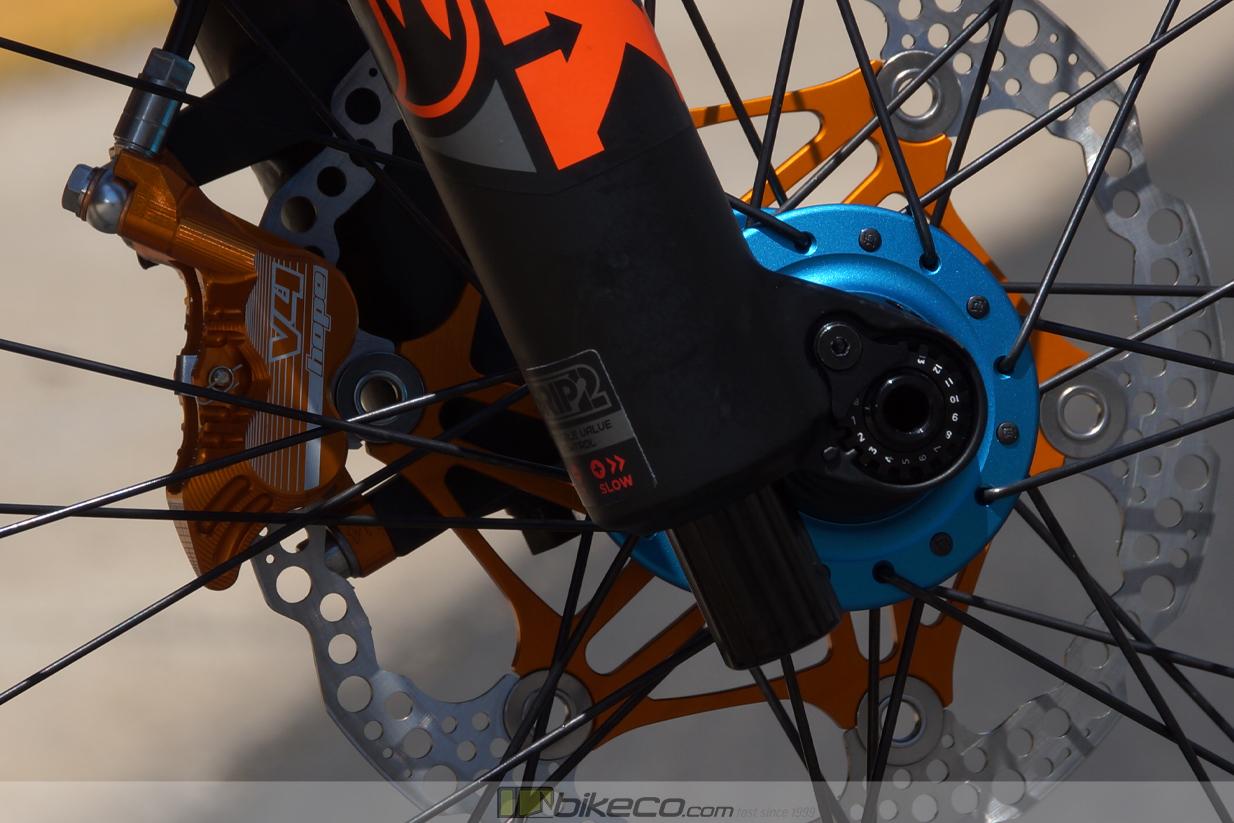 Detail of Chris King matte turquoise hub with Hope orange v4 caliper and orange 2 piece rotor