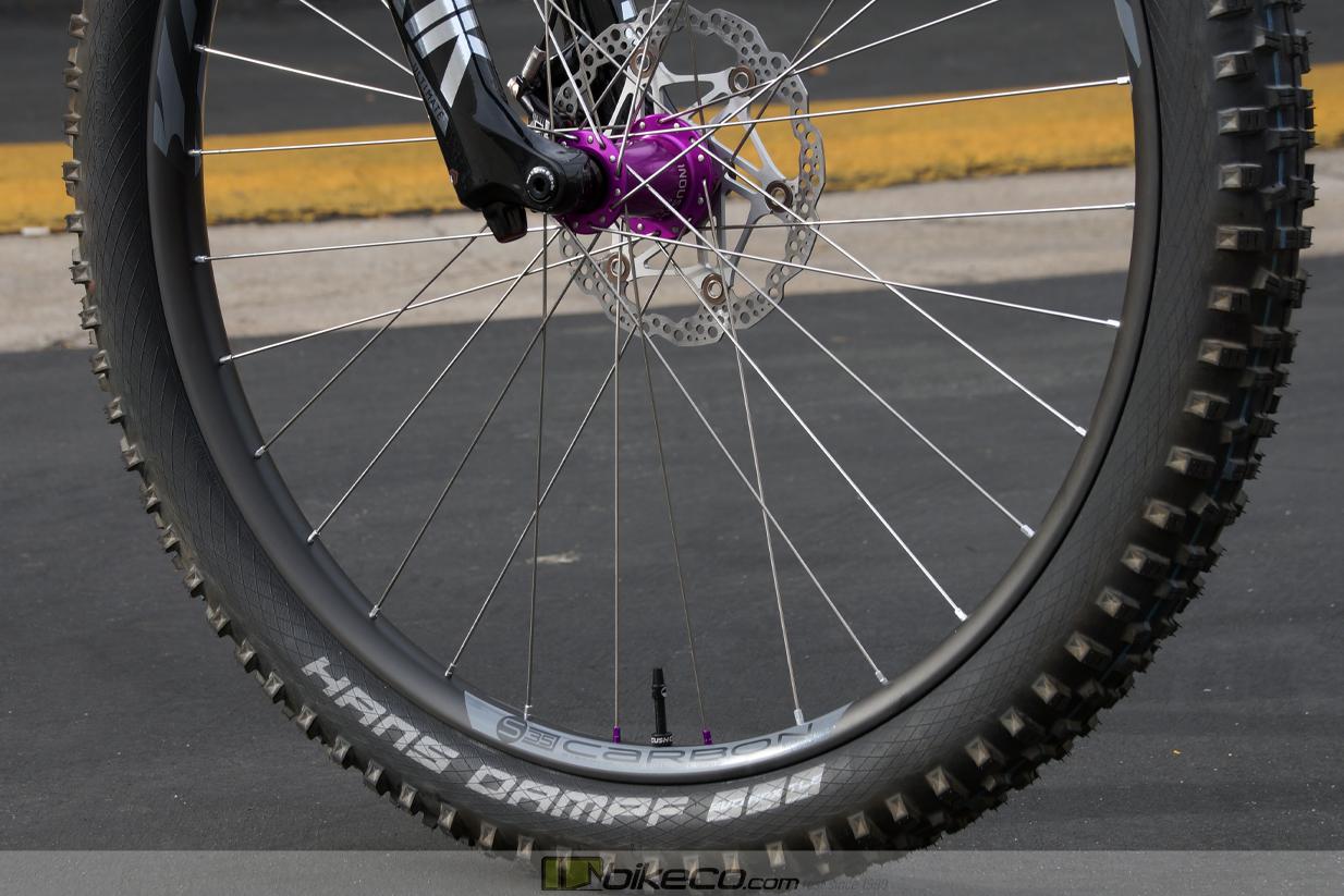 wheel detail shot of Industry Nine purple hub, silver spokes, Ibis S35 carbon rim with Hans Dampf tire on Ibis Ripmo custom